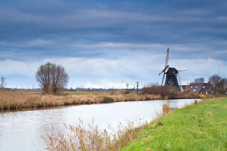 Dutch windmill by canal at clouded weather photo