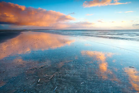 reflections of sky in North sea on sand beach photo