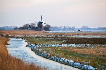 Dutch windmill by river in winter,  photo