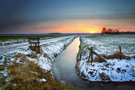 sunset reflected in frozen canal in Dutch farmland, Groningen photo