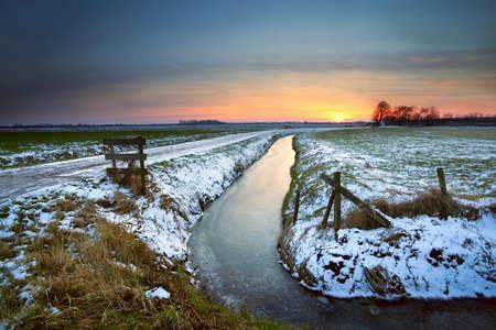 groningen: sunset reflected in frozen canal in Dutch farmland, Groningen