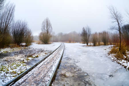 wooden road bridge through frozen lake in misty day Stock Photo - 18083362