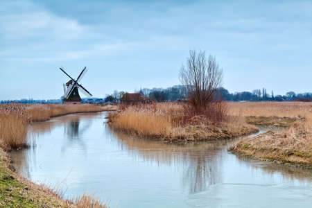 windmill in winter by frozen river, Groningen, Netherlands photo