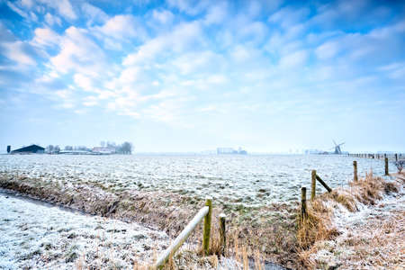 view with farmhouse and windmill in winter, Netherlands Stock Photo - 18122199