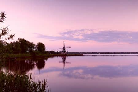groningen: Dutch windmill by lake at sunset, Groningen