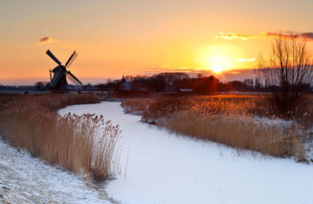 dramatic sunrise by Dutch windmill during winter photo