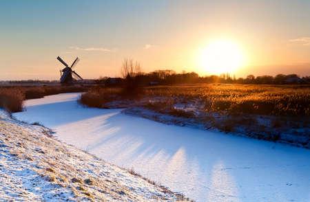 zonsopgang boven Nederlandse windmolen en bevroren gracht, Groningen