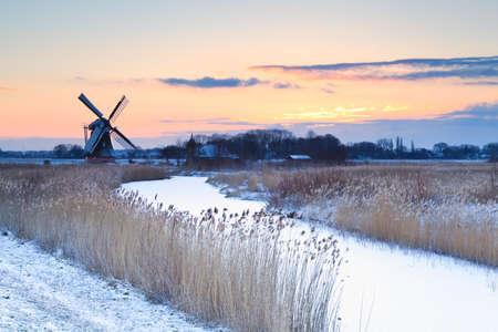 Nederlandse windmolen in de winter bij zonsopgang, Groningen Stockfoto