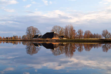 Dutch farmhouse by river before sunset, Holland Stock Photo - 18585815
