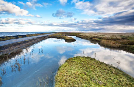 blue sky reflected in river by north sea, Friesland Stock Photo