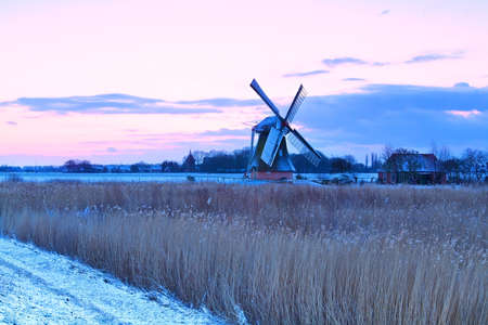 Dutch windmill in winter at sunrise, Holland photo