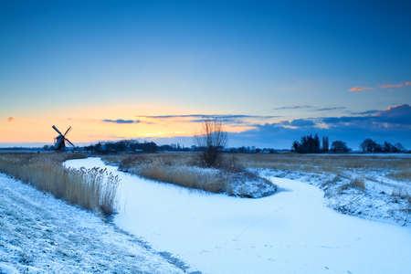 groningen: windmill by frozen river at sunrise, Groningen, Netherlands Stock Photo