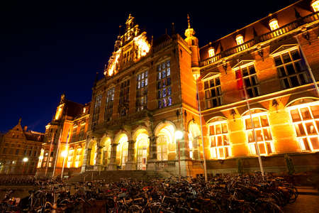 groningen: bicycles parking by University of Groningen at night, Netherlands