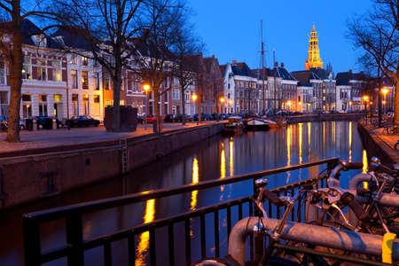 groningen: Nederlandse straat met fietsen bu kanaal in de schemering, Groningen