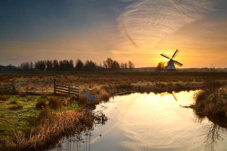 19223679-moulin-a-vent-hollandais-au-lever-reflete-dans-la-riviere
