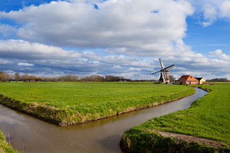 charming Dutch windmill by canal on green grassland, Holland photo
