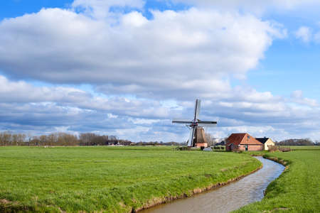 sunny day on Dutch farmland with windmill, Holland photo