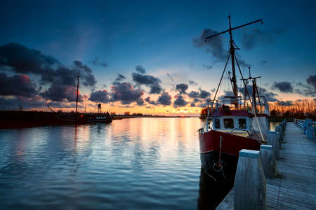 fishing ships at sunset in Zoutkamp, Netherlands photo