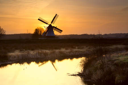 windmill silhouette at sunrise reflected in lake