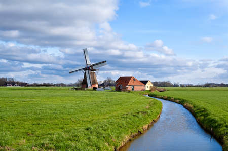 charming dutch windmill on green grasslands by river, Groningen photo