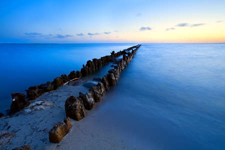 old wooden breakwater in North sea, Netherlands photo