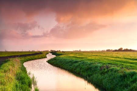 dramatic sunrise over canal in Dutch farmland, Groningen Stock Photo