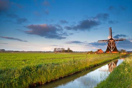 charmante Nederlandse windmolen bij zonsopgang, Groningen, Nederland