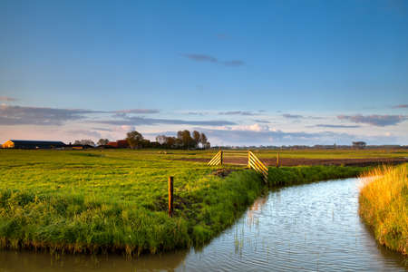 groningen: typische Nederlandse landbouwgrond met grachten bij zonsopgang, Groningen, Nederland