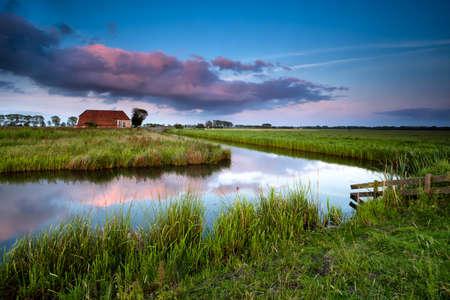groningen: little farmhouse and river at colorful sunset, Groningen, Netherlands