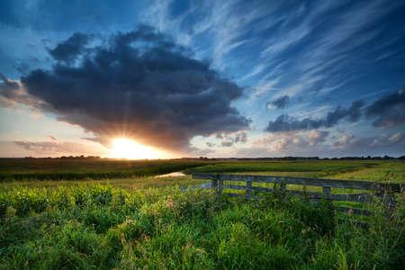 prachtige zonsondergang over groene zomer weiden, Groningen, Nederland