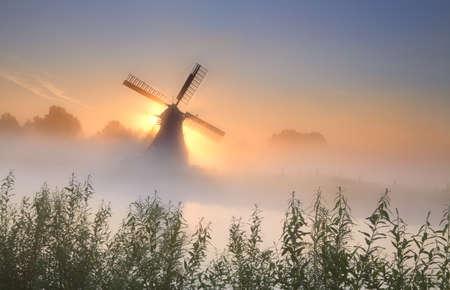 mistige sunrisebehind de windmolen nabij rivier