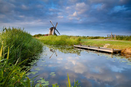 sulight: windmill and blue sky reflected in small lake with water lilies