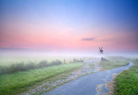 bicycle way to windmill in morning fog, Groningen, Netherlands