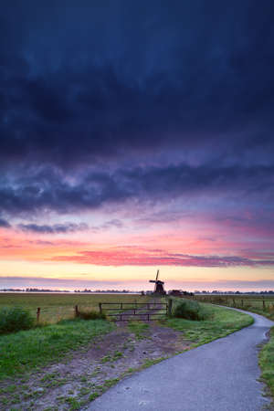 bicycle road to Dutch windmill in dramatic sunrise photo