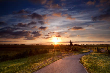 warm sunbeams by Dutch windmill at sunrise, Groningen, Holland photo