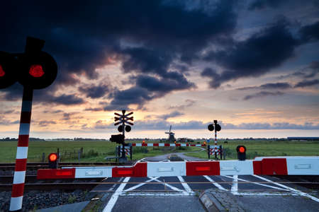 closed rail crossing with red sygnals at sunrise and windmill