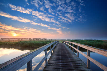 wooden bridge over river at summer sunrise