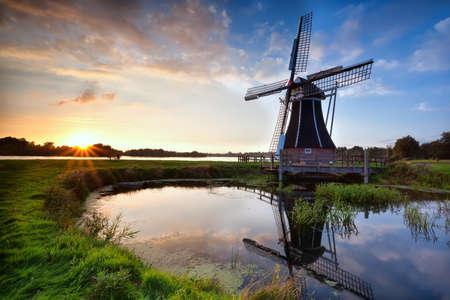 charmante Nederlandse molen weerspiegeld in het meer bij zonsondergang, Holland