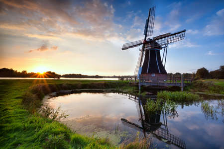 charming Dutch windmill reflected in lake at sunset, Holland
