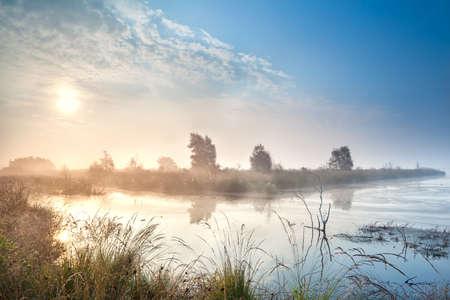misty sunrise over water in  bog, Fochteloerveen, Netherlands