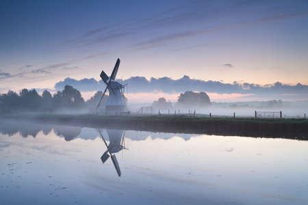 witte Nederlandse molen door de rivier in mistige zonsopgang, Groningen, Nederland