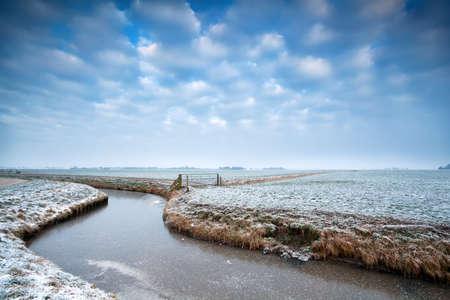 frozen canal on Dutch winter farmland, Groningen, Netherlands Banco de Imagens