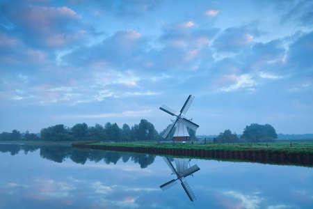 Dutch windmill close to river during calm pastel sunrise, Holland photo