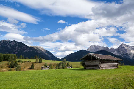 greem: few huts on greem meadows over blue sky in Bavarian Alps