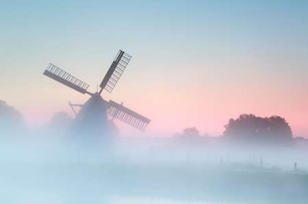 charming Dutch windmill in dense sunrise fog, Holland photo