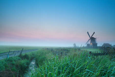 sunrise over Dutch farmland with windmill, Holland photo