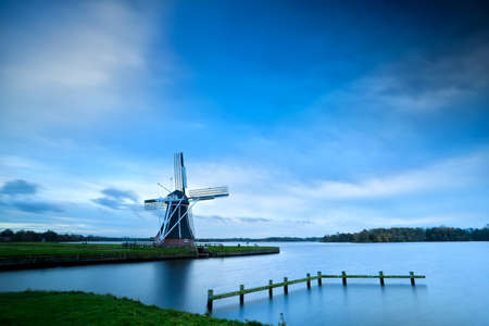groningen: Dutch windmill by lake with long exposure, Groningen, Netherlands Stock Photo