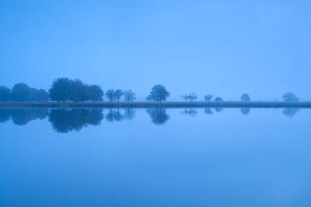friesland: tree reflections in lake water during misty morning, Friesland, Netherlands Stock Photo