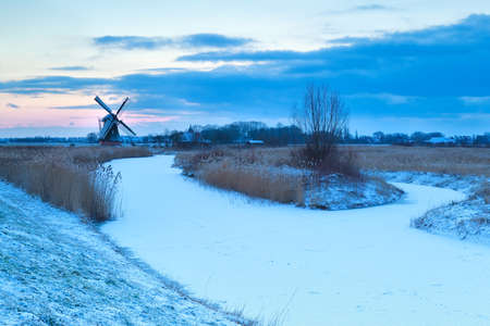 frozen river: windmill and frozen river in snow, Holland