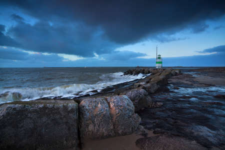 green lighthouse in dusk on North sea, Netherlands photo